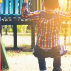 child swinging in park