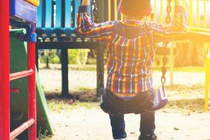 child swinging in park